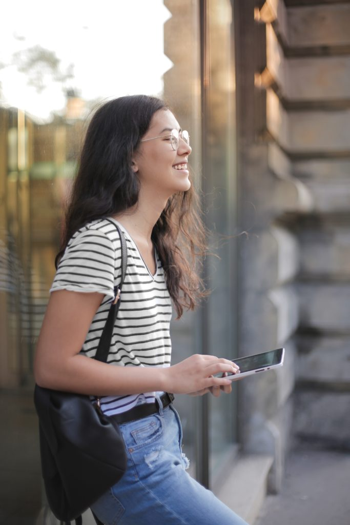 cheerful young woman using smartphone in street 3807742